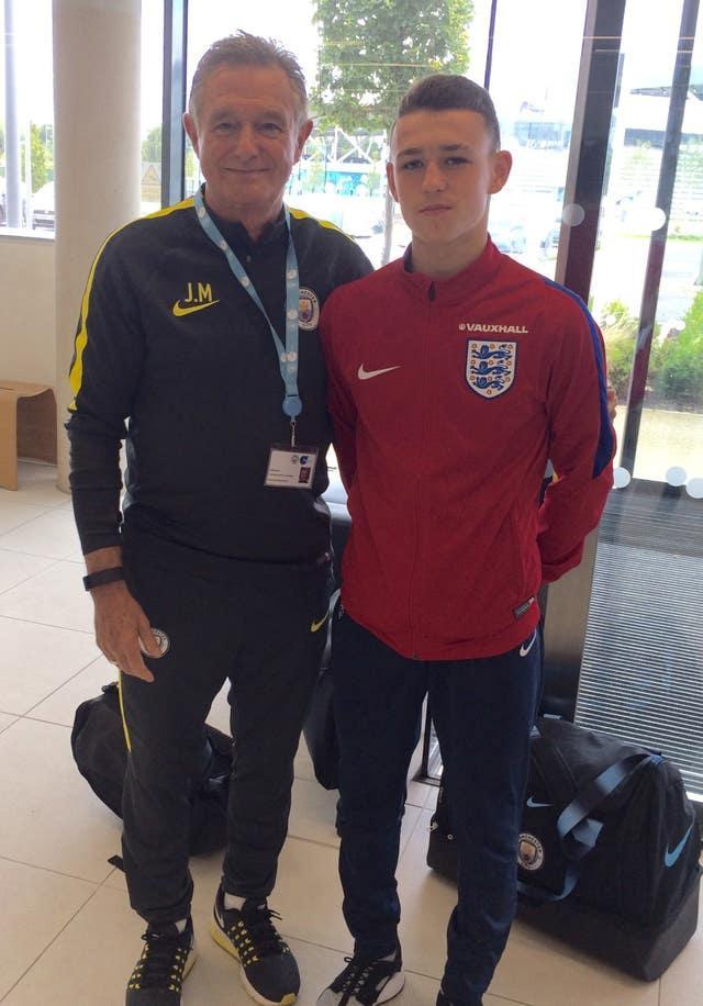 Phil Foden with his former youth team coach Joe Makin Handouts Photos