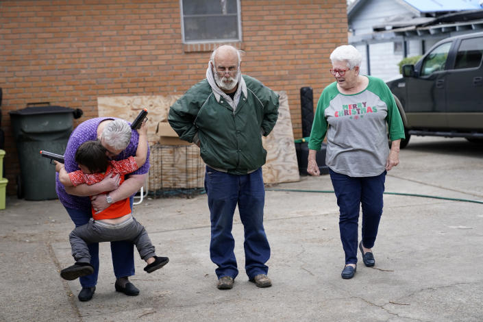 Janice Morgan, a church volunteer, hugs Conner Bourque as she arrives with Brenda Lee to bring him Christmas presents, in the aftermath of Hurricane Laura and Hurricane Delta, in Lake Charles, La., Friday, Dec. 4, 2020. Center is James Baker, who is living in a camper while his daughter lives in a tent outside of his heavily damaged home. (AP Photo/Gerald Herbert)