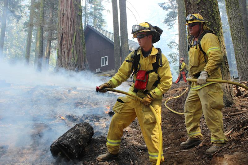 In this photo provided by the U.S. Forest Service, firefighters hose down a hotspot near a ranger station as they fight the Rim Fire in Yosemite National Park in California Sunday, Sept. 1, 2013. The massive wildfire is now 75 percent contained according to a state fire spokesman. (AP Photo/U.S. Forest Service, Mike McMillan)