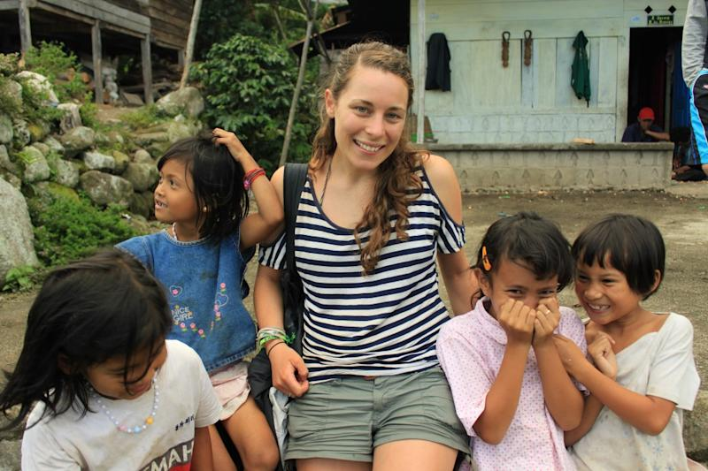 Sarah Frazer pictured in a white and black striped top with four children in a Brazilian village.