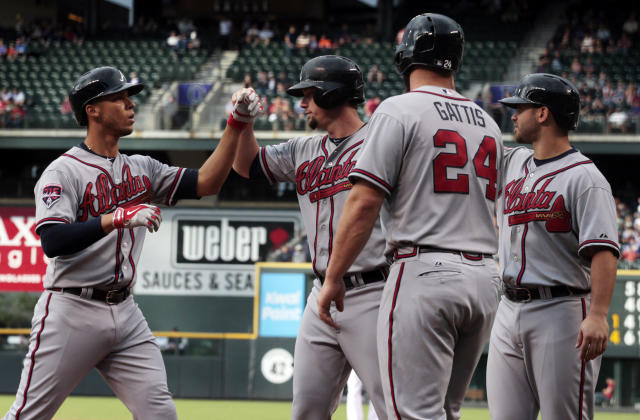 Atlanta Braves' Adrelton Simmons, left, is congratulated by Braves' Chris Johnson after Simmons grand slam home run that scored Johnson, Evan Gattis (24) and Tommy La Stella in the first inning of a baseball game in Denver on Tuesday, June 10, 2014. (AP Photo/Joe Mahoney)
