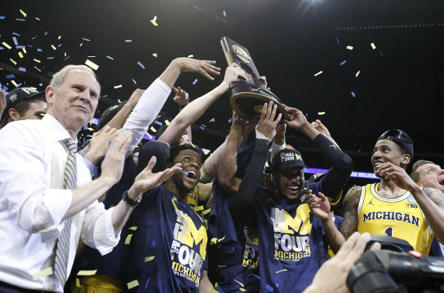 Michigan coach John Beilein, left, and players celebrate after the team's 58-54 win over Florida State in an NCAA men's college basketball tournament regional final. (AP Photo)
