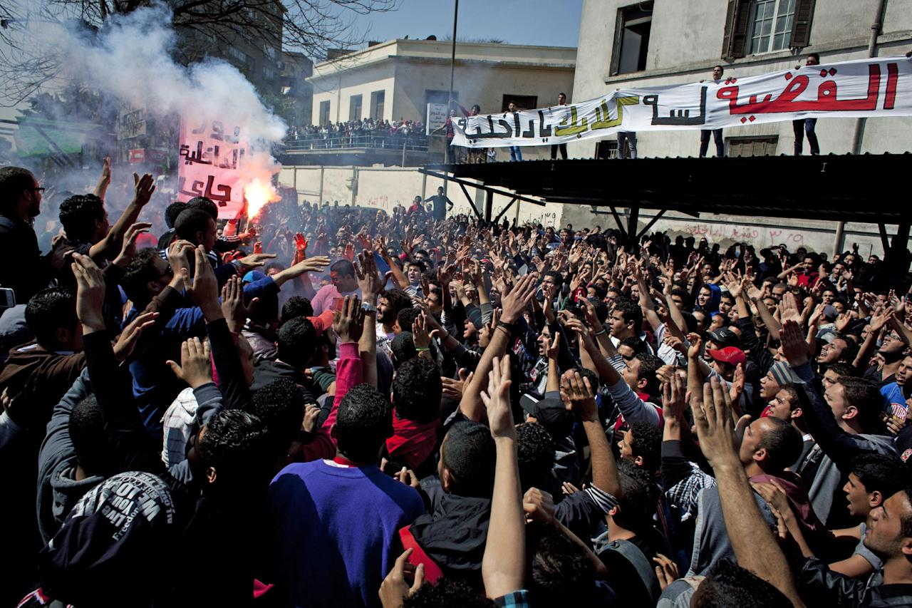 """Egyptian Ultras, hard-core soccer fans, use fireworks, and chant anti government and interior ministry slogans in front of the Giza security directorate, in Giza, Egypt, Wednesday, March 6, 2013. Hundreds of Ultras rallied to the Giza security directorate chanting anti government slogans, launching fireworks toward the security facility and setting a police pickup truck on fire. Partial translation of the banner in Arabic, reads, """"the case is not over, interior ministry's dogs remain."""" (AP Photo/Nasser Nasser)"""