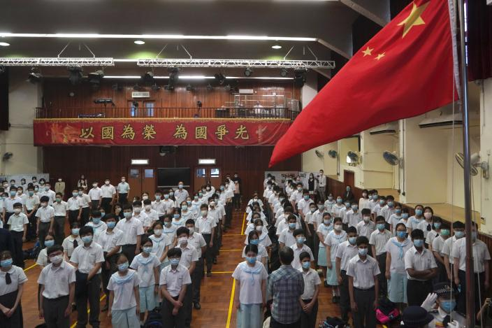 """Students attend a flag raising ceremony during the National Security Education Day at a secondary school, in Hong Kong, Thursday, April 15, 2021. Beijing's top official in Hong Kong on Thursday warned foreign forces not to interfere with the """"bottom line"""" of national security in Hong Kong, threatening retaliation even amid ongoing tensions between China and Western powers. (AP Photo/Kin Cheung)"""