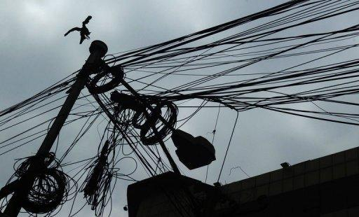 A bird lands on an electric pole wrapped with wires in Kolkata