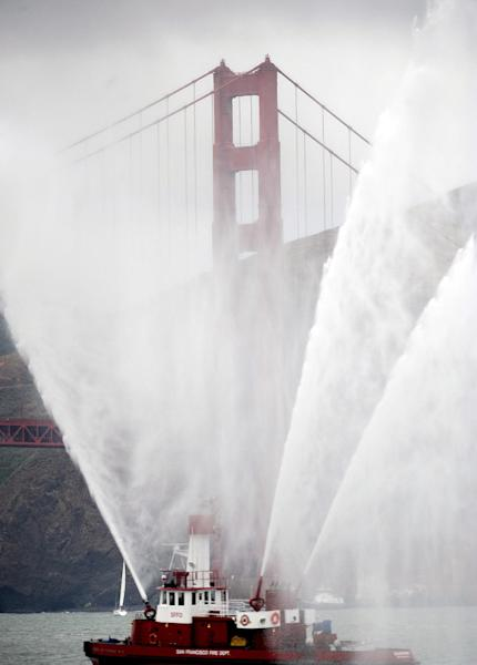 The Phoenix fireboat sprays plumes of water as part of the Golden Gate Bridge's 75th anniversary celebration on Sunday, May 27, 2012, in San Francisco. The commemoration included a vintage boat parade and a fireworks display slated for the evening. (AP Photo/Noah Berger)