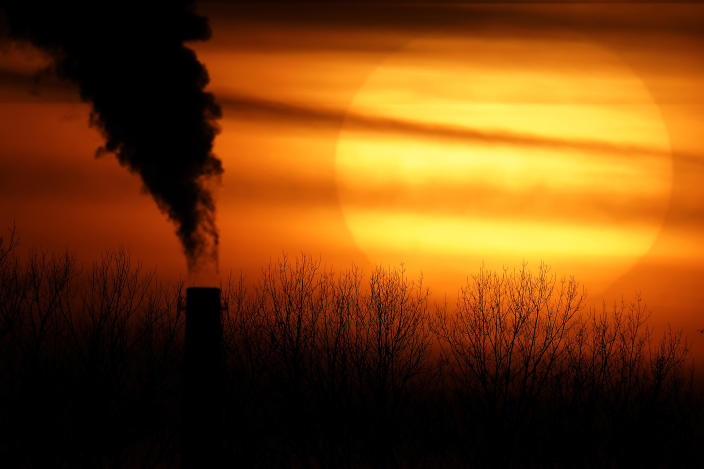 FILE - In this Feb. 1, 2021 file photo, emissions from a coal-fired power plant are silhouetted against the setting sun in Independence, Mo. President Joe Biden faces a vexing task as he convenes a virtual climate summit on Thursday. He is expected to present a nonbinding but symbolic goal to reduce greenhouse gas emissions that will have a tangible impact not only on climate change efforts in the U.S. but throughout the world. (AP Photo/Charlie Riedel, File)