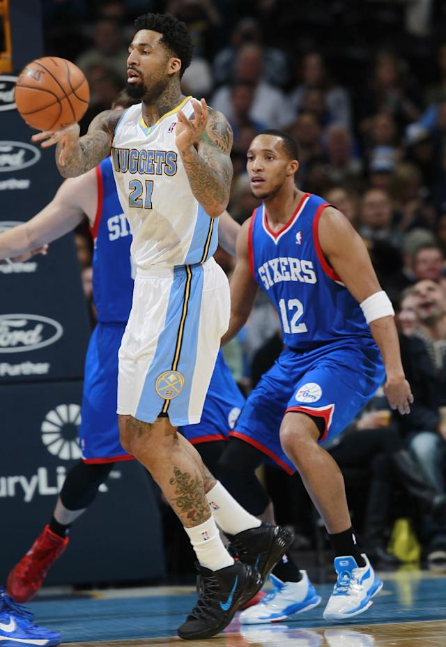 Denver Nuggets forward Wilson Chandler, front, passes the ball away from Philadelphia 76ers center Spencer Hawes, back left, and guard Evan Turner during the first quarter of an NBA basketball game in Denver on Wednesday, Jan. 1, 2014. (AP Photo/David Zalubowski)