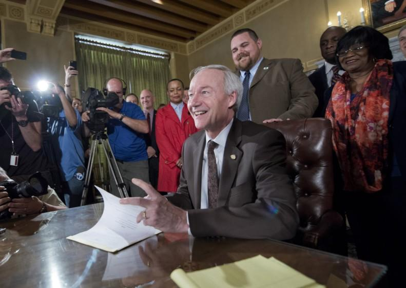 Arkansas Gov. Asa Hutchinson signs a reworked religious freedom bill into law after it passed in the House at the Arkansas state Capitol in Little Rock, Ark., Thursday, April 2, 2015. Lawmakers in Arkansas and Indiana passed legislation Thursday that they hoped would quiet the national uproar over new religious objections laws that opponents say are designed to offer a legal defense for anti-gay discrimination. (AP Photo/Brian Chilson) ORG XMIT: ARDJ110