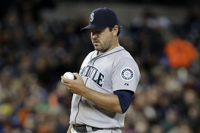 Seattle Mariners starting pitcher Joe Saunders looks at the ball after giving up a one-run single to Detroit Tigers' Victor Martinez in the sixth inning of a baseball game in Detroit, Monday, Sept. 16, 2013. (AP Photo/Paul Sancya)