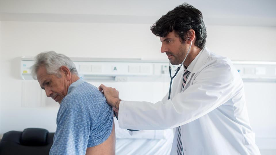Doctor doing his medical rounds at the hospital listening to a senior patients lungs.