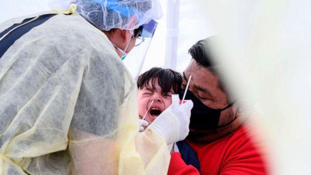PHOTO: Jose Vatres holds his son Aidin as nurse practitioner Alexander Panis takes a nasal swab sample for COVID-19 at a mobile testing station in a public school parking area in Compton, Calif., April 28, 2020. (Robyn Beck/AFP via Getty Images, File)
