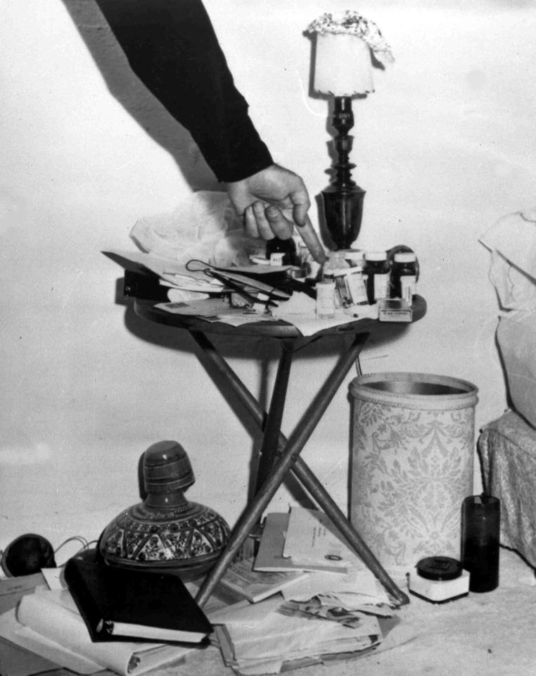 n this Aug. 5, 1962 file photo, a police officer points to an assortment of medicine bottles on the table beside the bed, right, in actress Marilyn Monroe's home in Los Angeles, Calif., where she was found dead. Monroe was 36-years-old. The 1982 District Attorney's report states that roughly 15 prescription bottles were seen at the scene, but only eight are reflected in the coroner's report. (AP Photo, File)