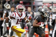 Washington State wide receiver Travell Harris (1) carries the ball while defended by Southern California safety Jaylin Smith (19) during the second half of an NCAA college football game, Saturday, Sept. 18, 2021, in Pullman, Wash. Southern California won 45-14. (AP Photo/Young Kwak)