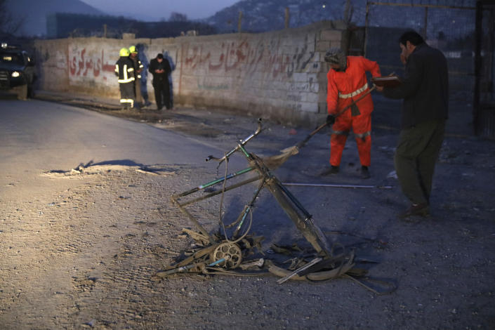 Afghan security personnel inspect the site of a bomb attack in Kabul, Afghanistan, Monday, Dec. 28, 2020. In two explosions Monday in the capital Kabul, multiple people were wounded, according to Kabul police. (AP Photo/Rahmat Gul)