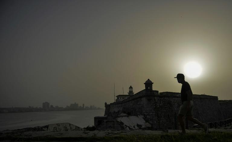A man walks near Morro Castle as a vast cloud of Sahara dust is blanketing the city of Havana, Cuba. (AFP Photo/YAMIL LAGE)