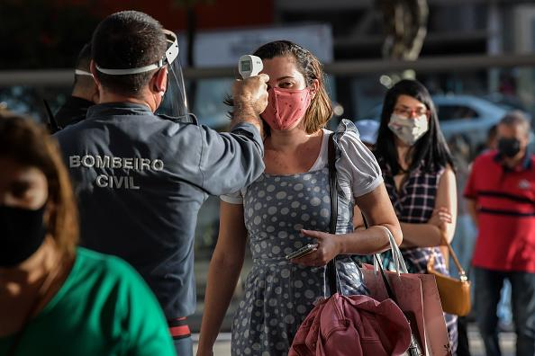 A costumer's temperature is checked as she enters a shopping mall after it reopened, at Paulista Avenue, in Sao Paulo, Brazil.
