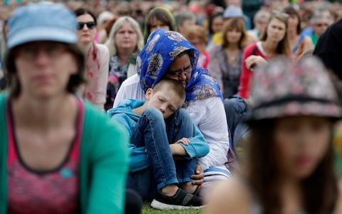 "A woman embraces a boy at the ""March for Love""  - Credit: Mark Baker/AP"