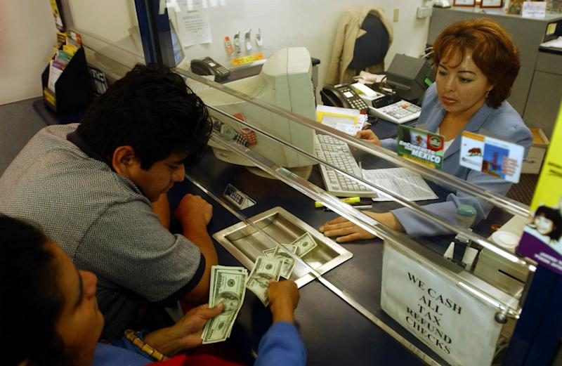 Alfonsa Morales, left, counts money she and her son Hector Gonzalez are handing to Eteldina Romero to be sent to Mexico, at Popular Cash Express #2 in Los Angeles, Monday, Dec. 30, 2002. Morales and Gonzalez sent $650 to a friend in a small village in Oaxaca as a New Year's gift. Money transfers from Mexican immigrants working in the United States to relatives back home increased to a record $10 billion in 2002, according to the Pew Hispanic Center in Washington, D.C. This year's amount is up $800 million from the previous year. (AP Photo/Ann Johansson)