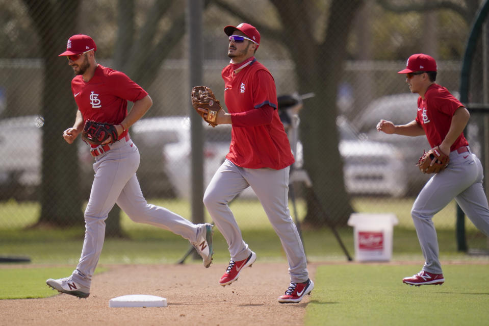 St. Louis Cardinals infielder Nolan Arenado, center, jogs out to the field with teammates Paul DeJong, left, and Tommy Edman during spring training baseball practice Monday, Feb. 22, 2021, in Jupiter, Fla. (AP Photo/Jeff Roberson)
