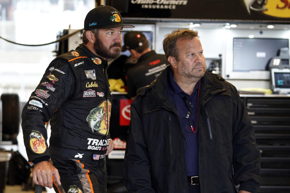 Martin Truex Jr, left, talks to a crew member before practice for Sunday's NASCAR Cup Series auto race at the Circuit of the Americas in Austin, Texas, Saturday, May 22, 2021. (AP Photo/Chuck Burton)
