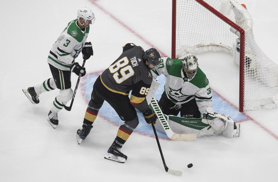 Dallas Stars goalie Ben Bishop (30) makes the save on Vegas Golden Knights' Alex Tuch (89) as Stars' John Klingberg (3) defends during the third period of an NHL hockey playoff game Monday, Aug. 3, 2020, in Edmonton, Alberta. (Jason Franson/The Canadian Press via AP)