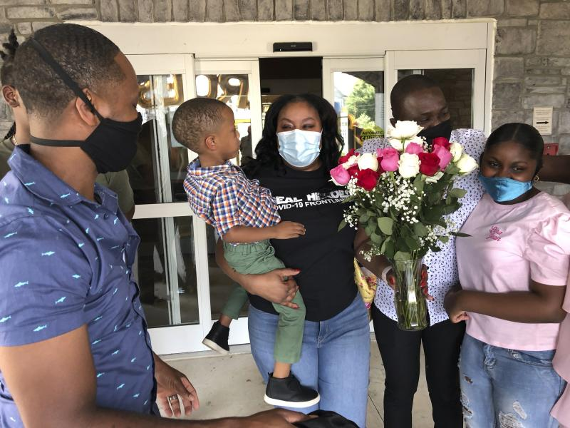 Teisha Roberts, center, a nursing director, is greeted by her family as she prepares to leave Park Springs elder care facility in Stone Mountain, Ga., Saturday, June 13, 2020. Workers who agreed to live at Park Springs to keep its residents safe from the coronavirus are back with their loved ones for the first time in nearly three months. (AP Photo/Sudhin S. Thanawala)
