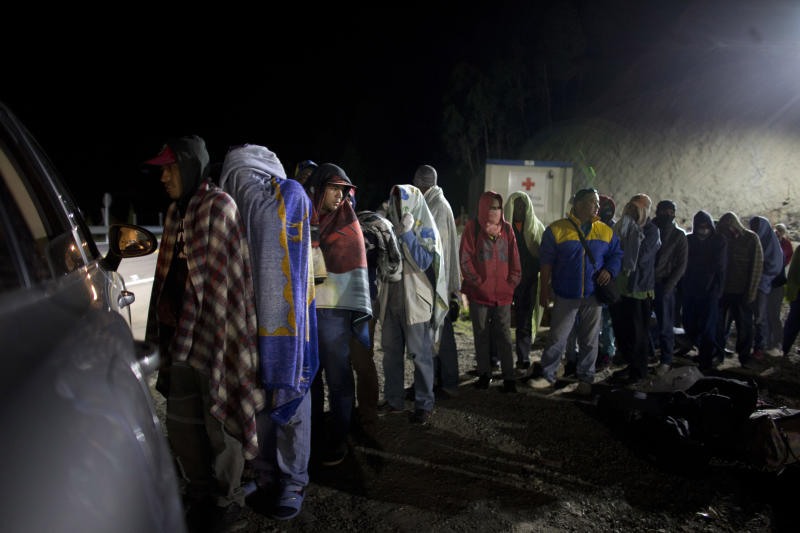 FILE - In this Aug. 31, 2018 file photo, Venezuelan migrants line up for free bread and coffee, donated by a Colombian family from their car, at a gas station in Pamplona, Colombia. A record 71 million people have been displaced worldwide from war, persecution and other violence, the U.N. refugee agency said Wednesday, June 18, 2019, an increase of more than 2 million from last year and an overall total that would amount to the world's 20th most populous country. Amid runaway inflation and political turmoil at home, Venezuelans for the first time accounted for the largest number of new asylum-seekers in 2018, with more than 340,000, or more than one in five worldwide last year. (AP Photo/Ariana Cubillos)