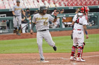 Pittsburgh Pirates' Josh Bell (55) scores past St. Louis Cardinals catcher Yadier Molina, right, during the eighth inning in the first game of a baseball doubleheader Thursday, Aug. 27, 2020, in St. Louis. (AP Photo/Jeff Roberson)