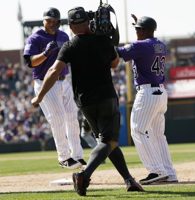 Colorado Rockies' Chris Iannetta, back left, jumps on first base after drawing a bases-loaded walk as first base coach Tony Diaz looks on in the ninth inning of a baseball game against the Los Angeles Dodgers, Sunday, Aug. 12, 2018, in Denver. (AP Photo/David Zalubowski)
