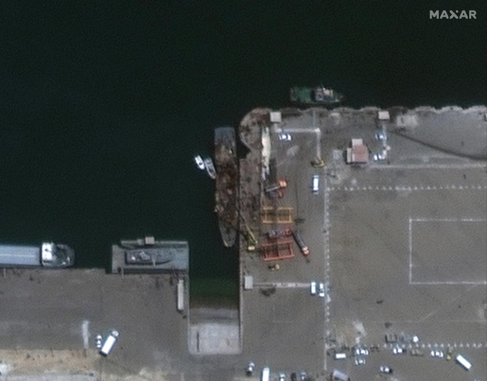 In this satellite photo provided by Maxar Technologies, the Iranian naval support vessel Konarak, center, is tied up at the port in Konarak, Iran, on Monday, May 11, 2020. A missile fired during an Iranian military training exercise mistakenly struck the naval vessel instead of its intended target in waters near the strategic Strait of Hormuz, killing and wounding a number of sailors, Iranian authorities said Monday. (Maxar Technologies via AP)