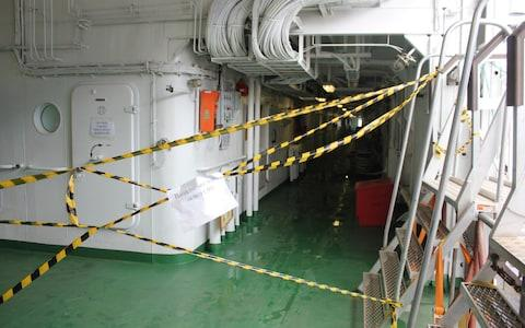 Hazard tape was stretched across several areas with signs instructing crew to access them through different corridors - Credit: Alec Luhn/For The Telegraph