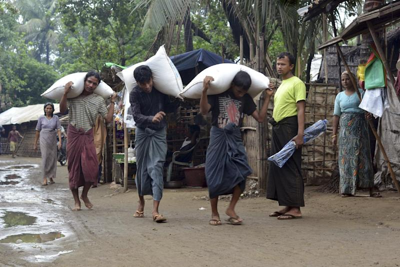 Men carry rice sacks as others look on, at a refugee camp in Sittwe, western Myanmar, Wednesday, May 15, 2013. A mass evacuation is taking place to clear low-lying camps in coastal areas of Bangladesh and Myanmar as cyclone Mahasen is predicted to make landfall late Thursday or early Friday, according to news reports. The mass evacuation has run into a problem as members of the displaced Rohingya minority have refused to leave because they don't trust Myanmar authorities. (AP Photo)