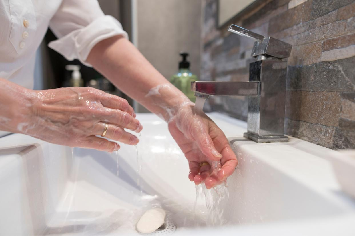 If you don't have a separate bathroom your sick partner can use, keep disinfecting wipes in your shared bathroom and wipe all communal surfaces down after use. (Photo: F.J. Jimenez via Getty Images)