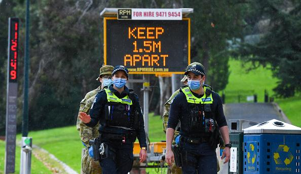 Police officers and soldiers patrol a popular running track in Melbourne.