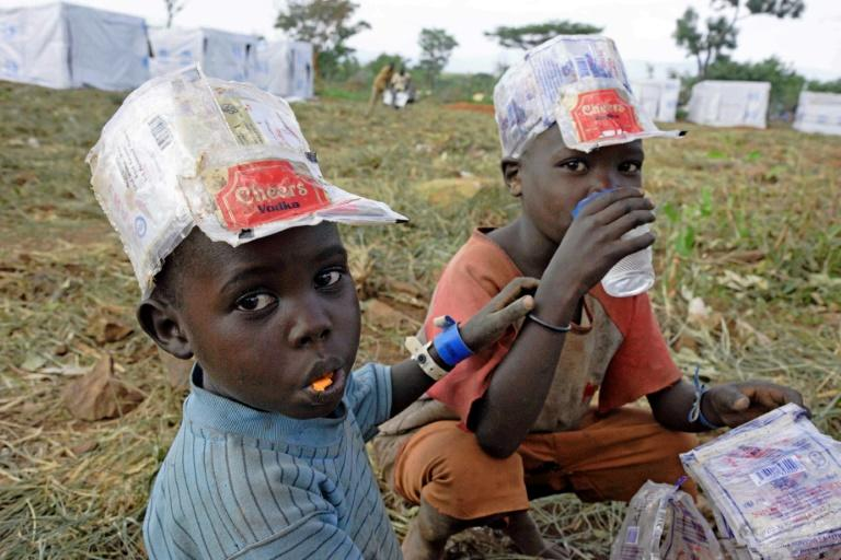 Newly arrived refugee children from South Sudan are given food food and drinks at the Ngomoromo border post, on the Ugandan side, where 830,000 South Sudanese have fled