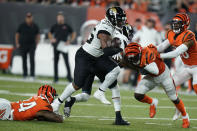 Jacksonville Jaguars' James Robinson (25) runs out of the tackle of Cincinnati Bengals' Vonn Bell (24) during the first half of an NFL football game, Thursday, Sept. 30, 2021, in Cincinnati. (AP Photo/Michael Conroy)