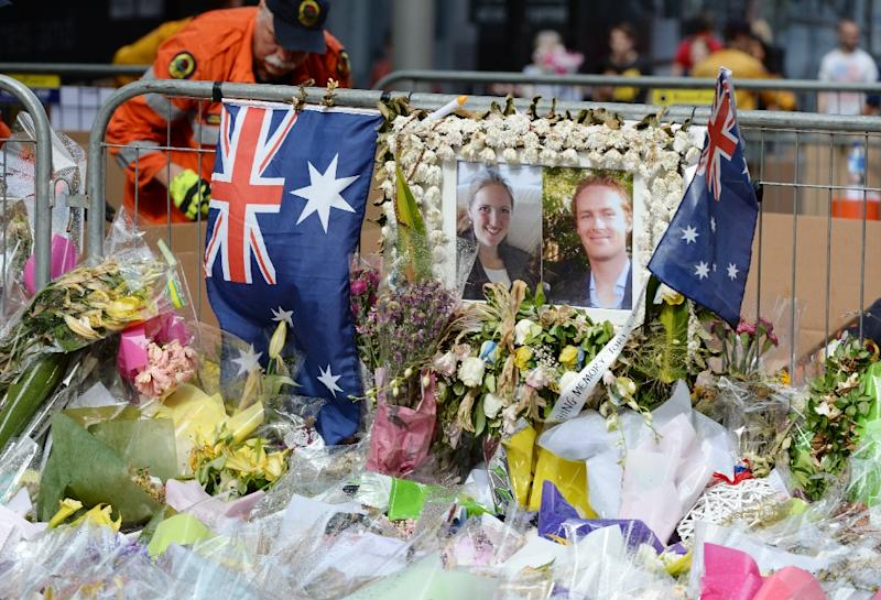 Photos of Katrina Dawson (L) and Tori Johnson are placed outside the Lindt cafe in Sydney on December 23, 2014, a week after a siege at the cafe which saw hostages Dawson and Johnson along with the gunman killed (AFP Photo/Peter Parks)