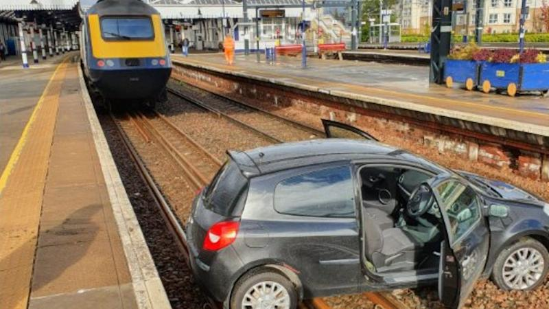 Car lands on train tracks at station