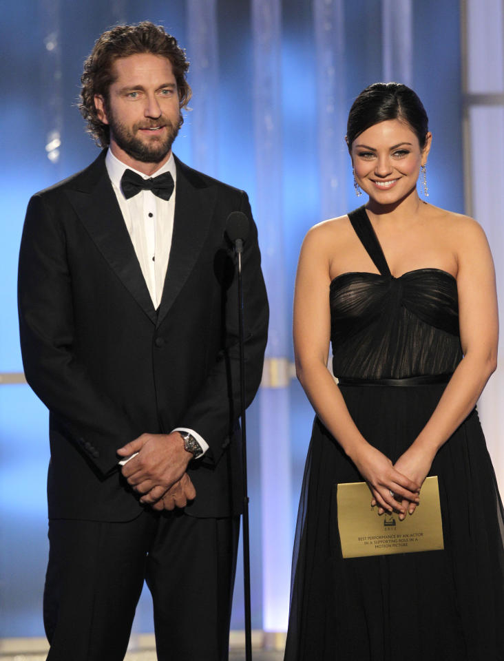 Gerard Butler and Mila Kunis present an award onstage during the 69th Annual Golden Globe Awards in Beverly Hills, California, on January 15, 2012. (Photo by Paul Drinkwater/NBC via Getty Images)