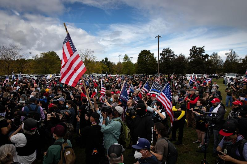Several hundred members of the Proud Boys in a park raise U.S. and Trump flags