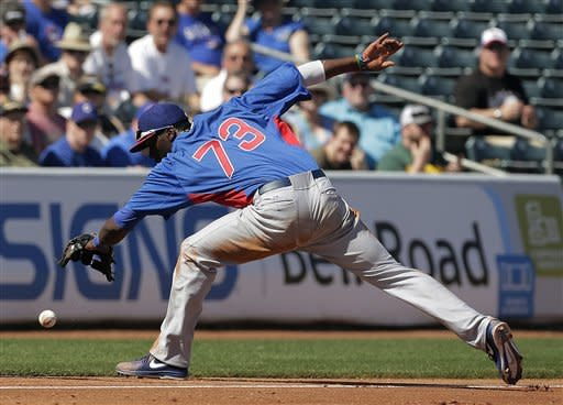 Chicago Cubs shortstop Junior Lake tries to get control of a single hit by Texas Rangers' Jurickson Profar during the second inning of an exhibition spring training baseball game, Wednesday, March 6, 2013, in Surprise, Ariz. (AP Photo/Charlie Riedel)