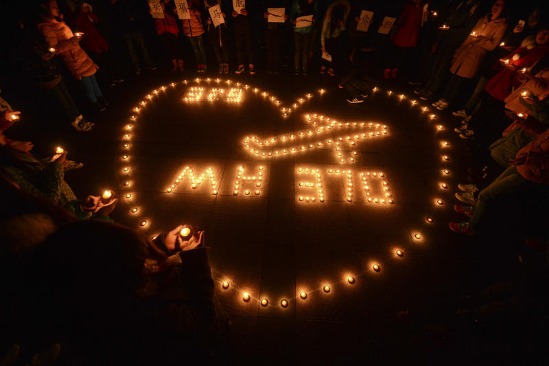 In this Thursday, March 13, 2014 photo, university students hold a candlelight vigil for passengers on the missing Malaysia Airlines Flight 370 in Yangzhou, in eastern China's Jiangsu province. With the search for the missing airliner entering its eighth day, scenarios involving piracy or hijacking are increasingly being talked about as possible explanations for the disappearance of the Boeing 777 with 239 people on board. (AP Photo) CHINA OUT