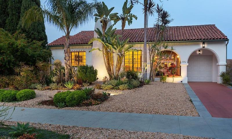 A home with a slate roof and Spanish arches stands before a garden with palms and succulents.