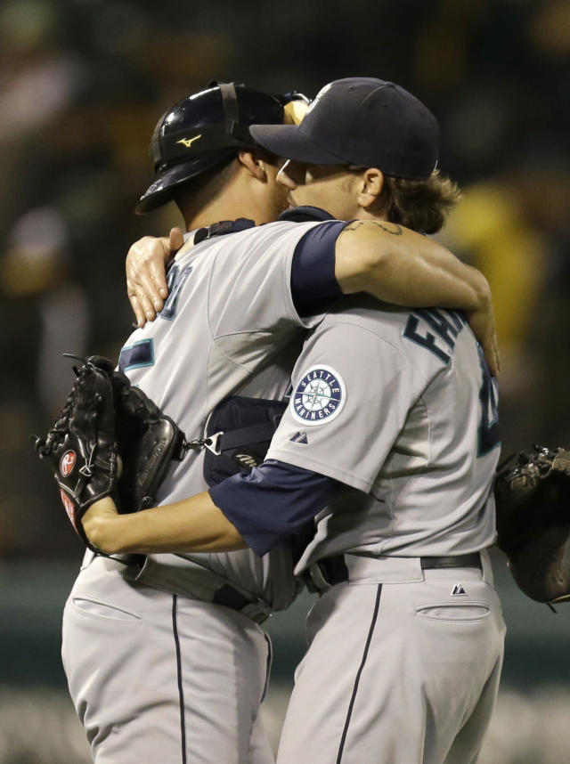 Seattle Mariners' Humberto Quintero, left, embraces Danny Farquhar at the end of a baseball game against the Oakland Athletics Tuesday, Aug. 20, 2013, in Oakland, Calif. Seattle won, 7-4. (AP Photo/Ben Margot)
