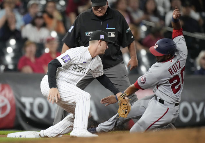 Colorado Rockies third baseman Ryan McMahon, left, tags out Washington Nationals' Keibert Ruiz as he tries to advance from first to third base on a single hit by Luis Garcia in the fourth inning of a baseball game Monday, Sept. 27, 2021, in Denver. (AP Photo/David Zalubowski)