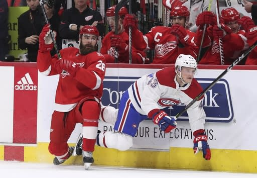 Detroit Red Wings right wing Luke Witkowski (28) checks Montreal Canadiens left wing Daniel Carr (43) during the first period of an NHL hockey game, Thursday, April 5, 2018, in Detroit. (AP Photo/Carlos Osorio)