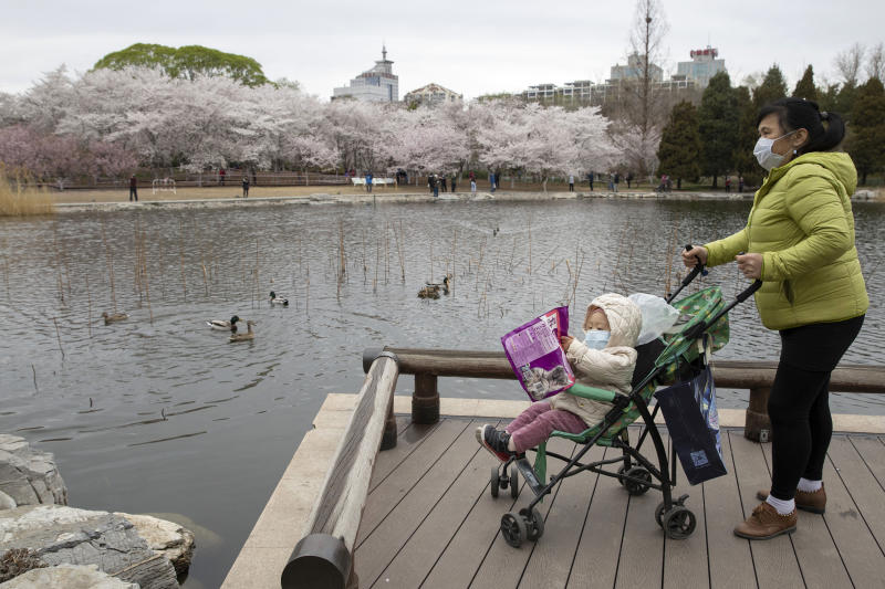 A woman pushes a child on a pram across from cherry blossoms at the Yuyuantan Park in Beijing on Thursday, March 26, 2020. While many of the city's world-famous tourist sites, including the sprawling Forbidden City ancient palace complex, remain closed, spring weather and budding cherry blossoms are coaxing outdoors citizens who have been largely confined to home for the last two months. For most people, the new coronavirus causes mild or moderate symptoms, such as fever and cough that clear up in two to three weeks. For some, especially older adults and people with existing health problems, it can cause more severe illness, including pneumonia and death. (AP Photo/Ng Han Guan)