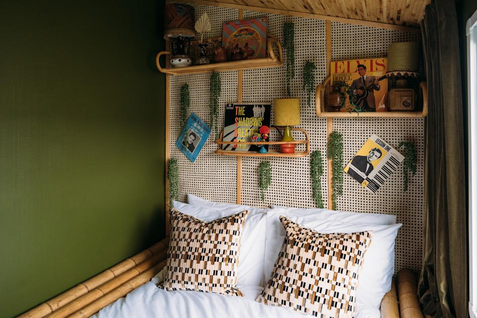 """AFTER: Anna replaced the single beds for a double and created a bed frame out of bamboo for a tiki feel. The wall opposite the bed (not pictured) was covered with a bronze-acrylic mirror to create the illusion of extra space. Most of the furnishings, including the rattan shelves and lampstands, are vintage. Part of the """"Jungle Room""""'s mood board was Elvis Presley's Jungle Room in Graceland. """"So tacky and ridiculous,"""" says Anna. """"But so fun."""""""