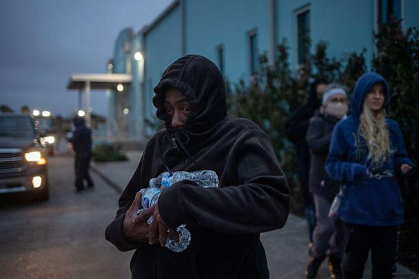 PHOTO: A woman carries bottled water she received from a warming center and shelter after record-breaking winter temperatures, as local media report most residents are without electricity, in Galveston, Texas on Feb. 17, 2021. (Adrees Latif/Reuters)
